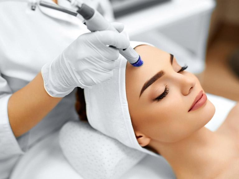 Medycyna estetyczna, twarz kobiety, urządzenie gładzące czoło